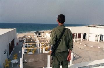 جندي احتلال يحرس فندقا في المستوطنات أمام بحر غزة