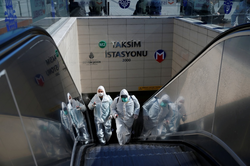 Municipality workers in protective suits disinfect entrance of Taksim metro station in central Istanbul