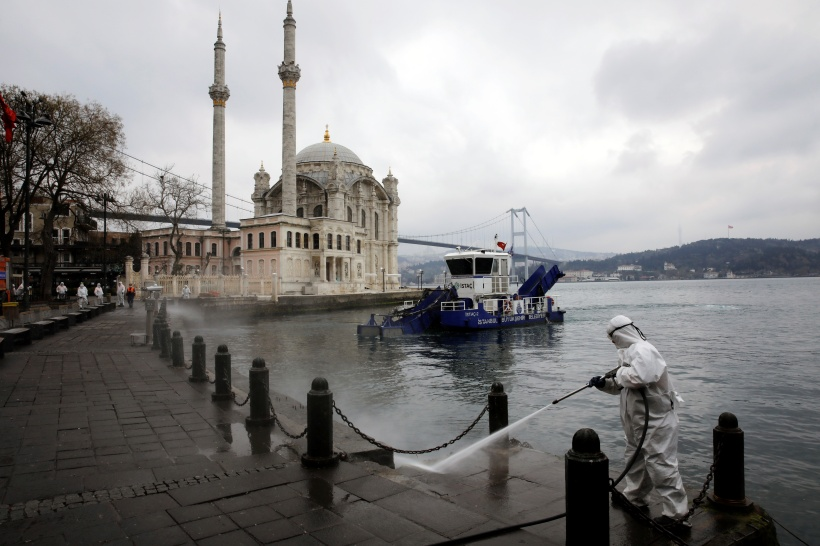 A worker sprays disinfectant outside Ortakoy Mosque, to prevent the spread of coronavirus disease (COVID-19), in Istanbul